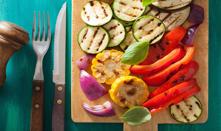 grilled vegetables on a wood cutting board