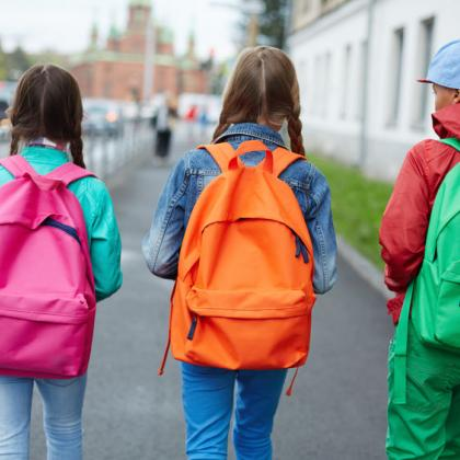 Elementary school kids with bright colored backpacks walking to school
