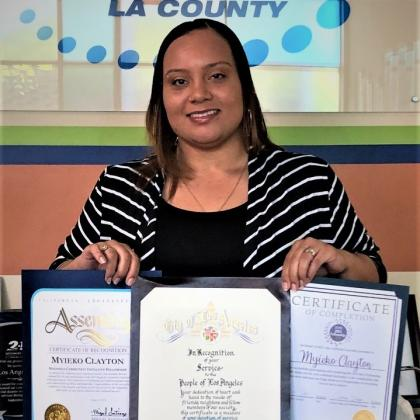 "Myieko ""Kiki"" Clayton posing with certificates from the City of Los Angeles, California State Assembly, and Magnolia Community Initiative for successfully completing the MCI Fellowship program in 2019"