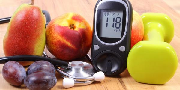 Blood sugar monitor, fruit, and stethoscope
