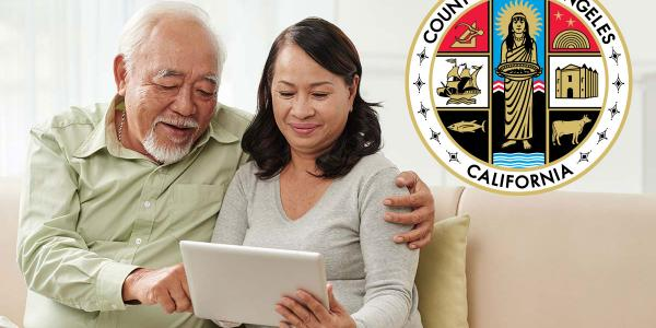 elder couple hugging and looking at electronic